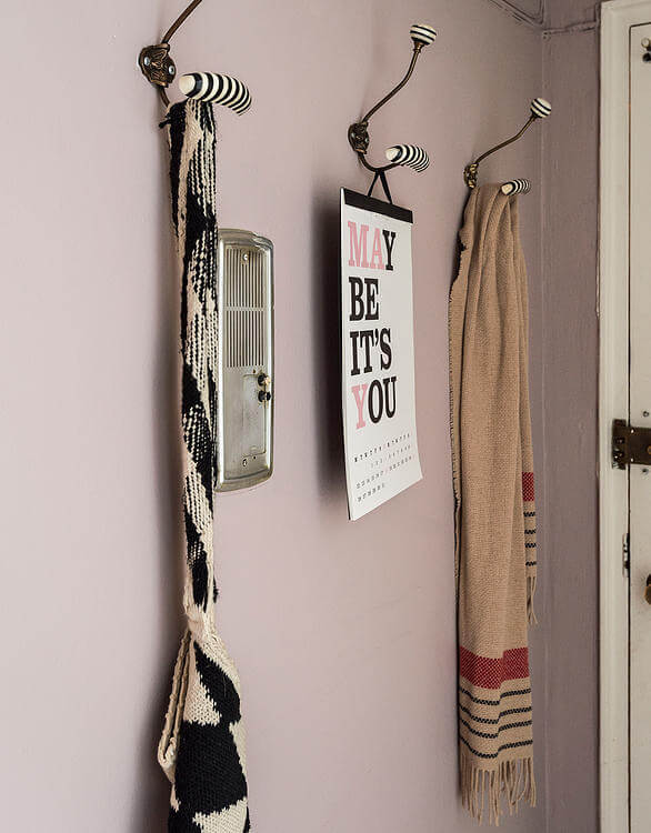A trio of striped coat hangers stand beside the front door and vintage intercom.