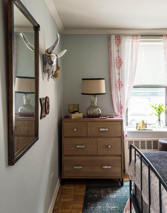 Moving back, we see the patterned hardwood flooring below the bedroom. Dresser stands beside the moderately sized window, with cropped drapes allowing abundant light in.