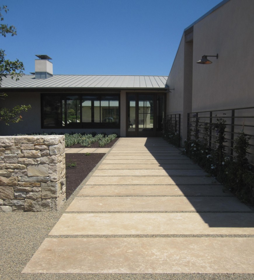 The walkway runs along the side of the building to sliding-glass doors into the home. Large glass windows on either side of the home allow visitors to see almost through the building.