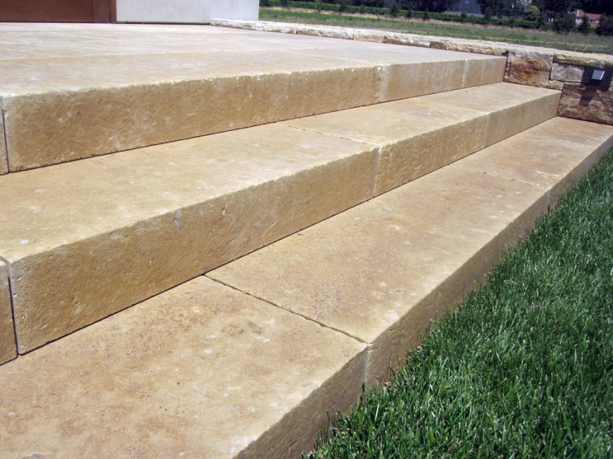 A close up of the limestone steps that lead down into the manicured lawn from the patio. The texture and warmth of the stone is inviting and elegant.