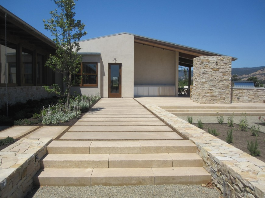The front entryway is also lined in limestone, with large, monolithic steps leading up from gravel to a manicured pathway. The sides are also limestone, pieced together to form a solid barrier. The wrap around patio is also in limestone.