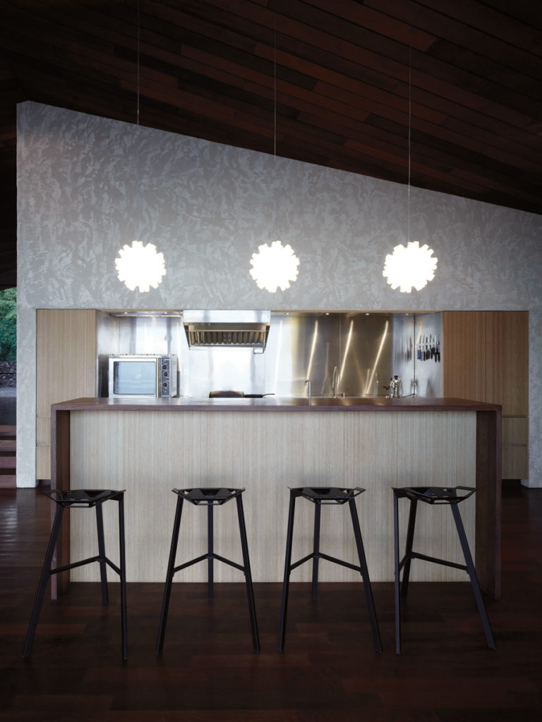 With dark wood wrapping around a lighter wood body, the island's raised dining half contrasts nicely with the geometric black metal bar stools.