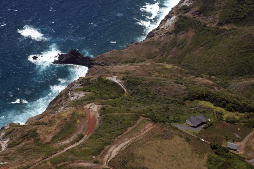 As seen from an aerial shot, the folded roof home nearly blends in with its surroundings. The increasingly sloped cliff face spreads to the left from this angle, ending in the rocky shores below.