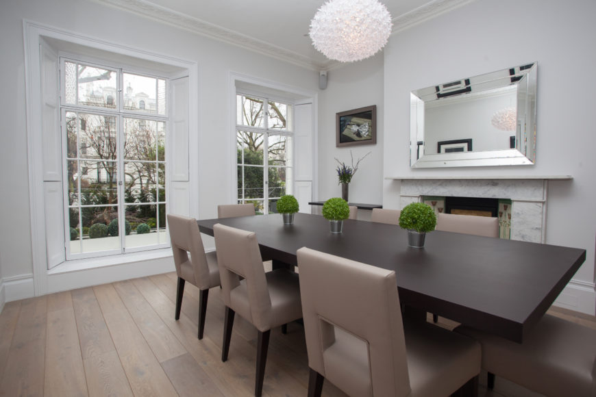 The dining room is an exercise in restrained elegance, featuring a minimalist dark wood table as its centerpiece, surrounded by leather upholstered Parson chairs. The white walls and door height windows surround a natural hardwood floor, while marble fireplace stands to the right below a large mirror.