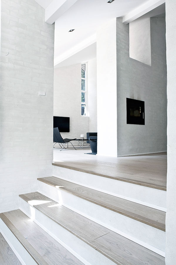Angling upward over the stairs, we see a wall cutout above the fireplace, allowing for light to spill through.