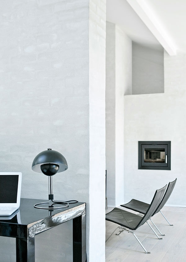 Beside the living room space, we see a subtle office area, with a large glossy black desk holding a semi-spherical black lamp with metal frame.