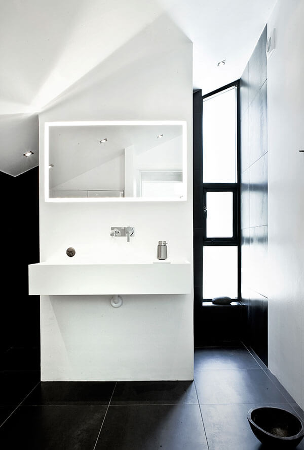 Master bath, contrasting with the body of the home, appears in black floor and wall tiles, punctuated by an all-white vanity at center.