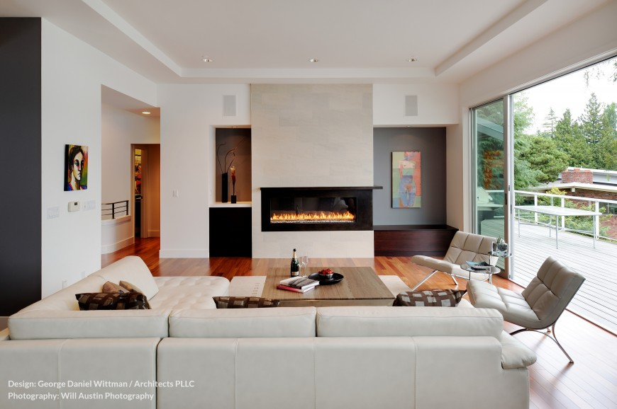 The living room opens almost entirely to the upper balcony, with large sliding glass panels as seen at right. A modern gas fireplace dominates the view, while white leather gracing the sectional and chairs contrasts with rich hardwood flooring.