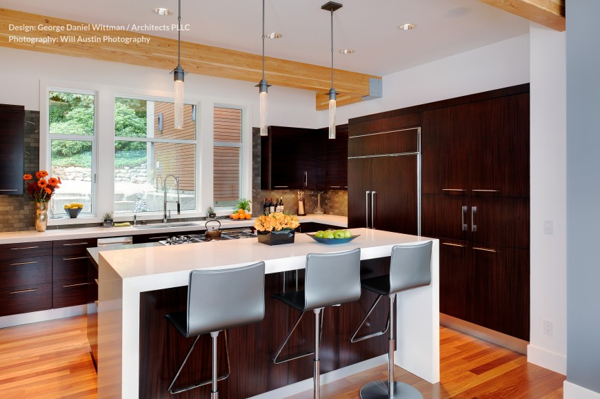 The kitchen is defined by the contrast between dark wood cabinetry and stark white walls, which extends to the large central island. Subtle brick tile work acts as a backsplash, flanking the large over-sink window.