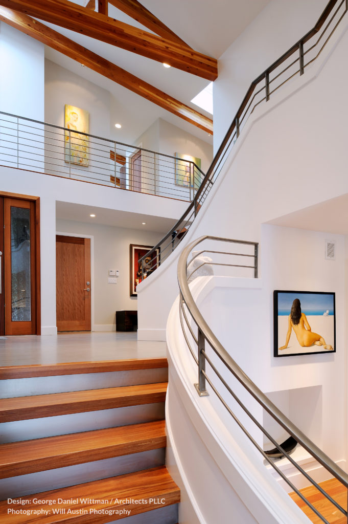The grand central staircase is a curved affair, featuring natural wood planks between white frames, with brushed metal railings. The upper level holds a catwalk overlooking the first floor.