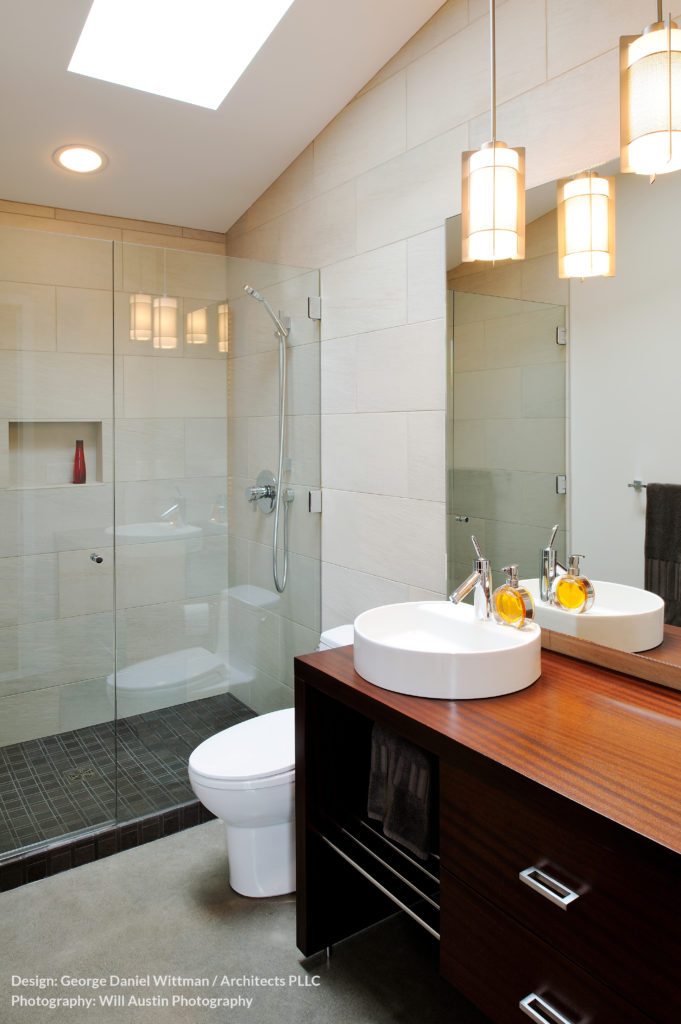 A secondary bathroom repeats the rich wood and white tone contrast of the main body of the home, with a white vessel sink standing on the wood vanity with black cupboards at right. All-glass shower enclosure adds to the contemporary look.