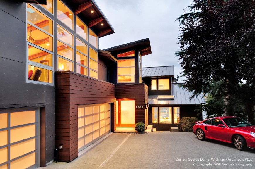 The front exterior of the home soars with glass panels reaching toward the sloped roof. Mixture of metal, cedar, and light glowing through the glass creates an intricate visual palette.