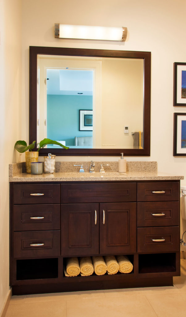 The guest bathroom has a lovely dark wood vanity with chrome pulls. The granite countertop is topped by a large mirror. Towel storage is tucked neatly into the bottom of the vanity.