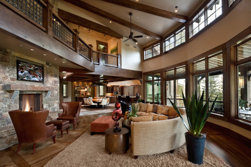In the sprawling, open design living room, we see a full two stories of windows reaching toward the exposed wood beam ceiling, allowing natural light to spread across the expanse of hardwood flooring. A large rounded sectional stands at center before the stone fireplace, with catwalk hallway overhead.