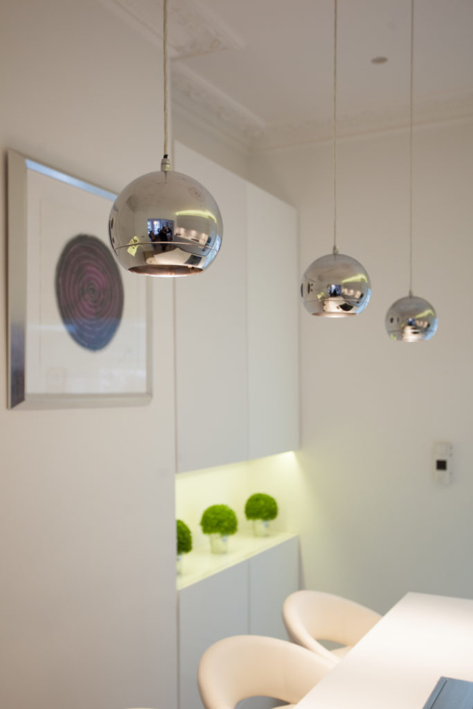 A small glimpse of the kitchen reveals stark white cabinetry and a trio of chromed sphere pendant lights. Under-cupboard lighting highlights small potted plants, adding a touch of nature to the room.