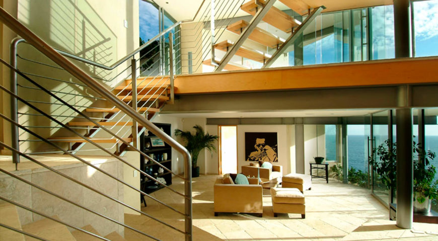 The open design steel and wood stairs lead toward a lower living room space, with tile flooring and matching beige furniture.