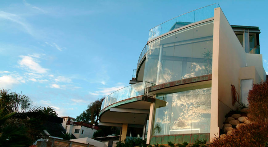Exterior view of a cliff-top glass home overlooking the ocean designed by McClean Design