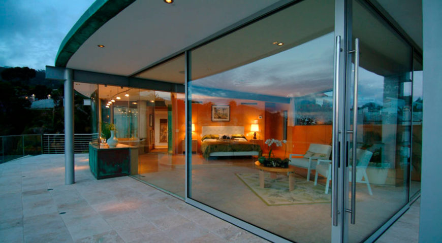 Seen from outside, the master bedroom holds a full living room style seating area for perfect ocean views, and sliding glass panels for balcony access.