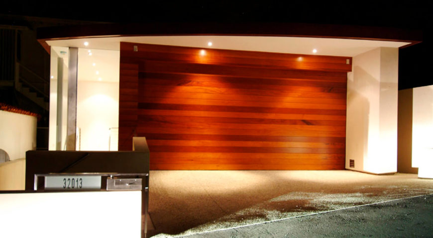 The garage as seen from the road, with a high contrast courtesy of rich hardwood door pairing with white structure.