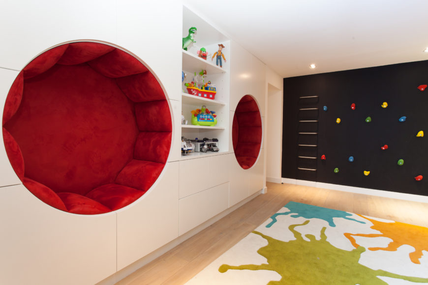A pair of bright red circular wall-cutout seats appear on this side of the room, adding a flamboyant detail to the already colorful space.