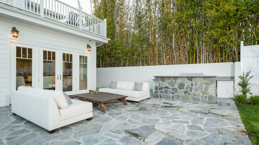 The backyard patio is in gray flagstone with a heavy, solid coffee table between two cozy sofas just below the balcony outside of the master bedroom.