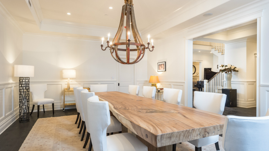The more formal dining room has a natural wood slab table with contemporary high-backed chairs in white. The large iron chandelier hanging above adds to the rustic charm invoked by the table.