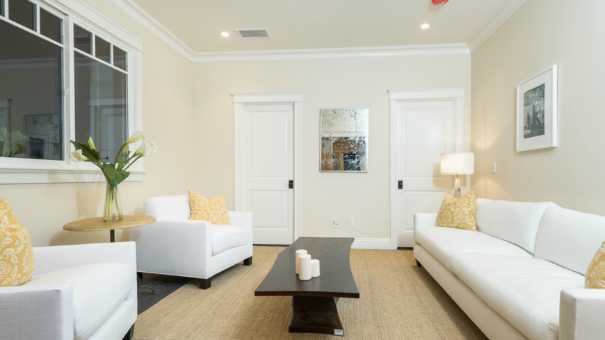 A casual sitting room has lovely white contemporary furniture accented with pale yellow pillows that complement the natural fiber rug. The dark natural wood coffee table has a unique shape.