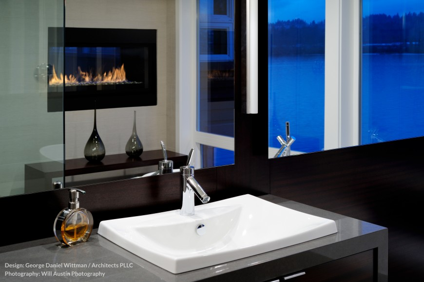The master bath, in contrast with the rest of the home, is awash in dark tones. The dual vanity stands below a dark wood wall framing a trio of large mirrors, reflecting the gas fireplace.