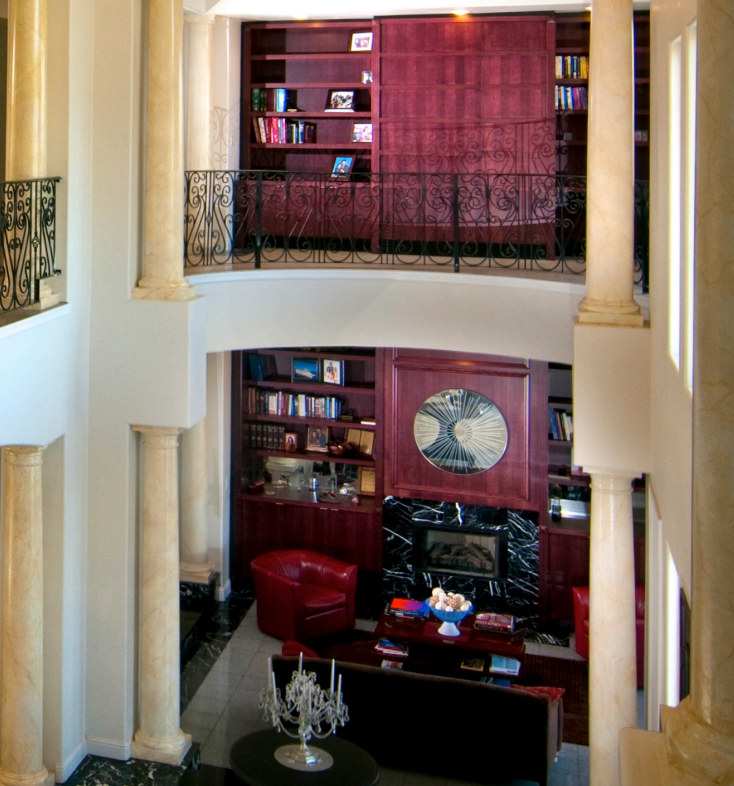 The split level library, seen from the upper level.  The bottom half doubles as a den, with rich red leather furniture and tile flooring.