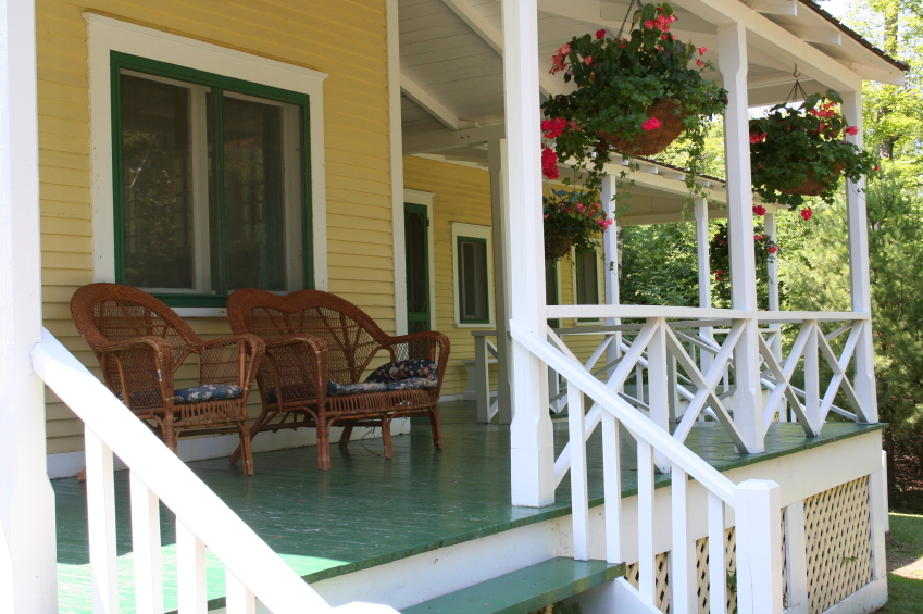 Porch Design Ideas you can not only grow flowers in planters but also put them in a door wreath This Wrap Around Porch Has Green Decking And White Railings With Country Style Charm