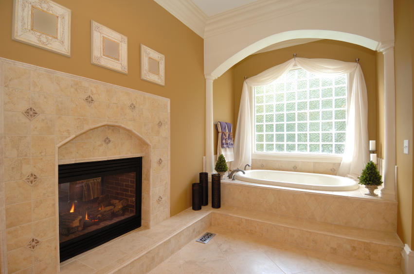 Soft yellow hued walls pair with warm beige tile in this bathroom, featuring a picture window soaking tub beside a massive tile-surrounded fireplace.