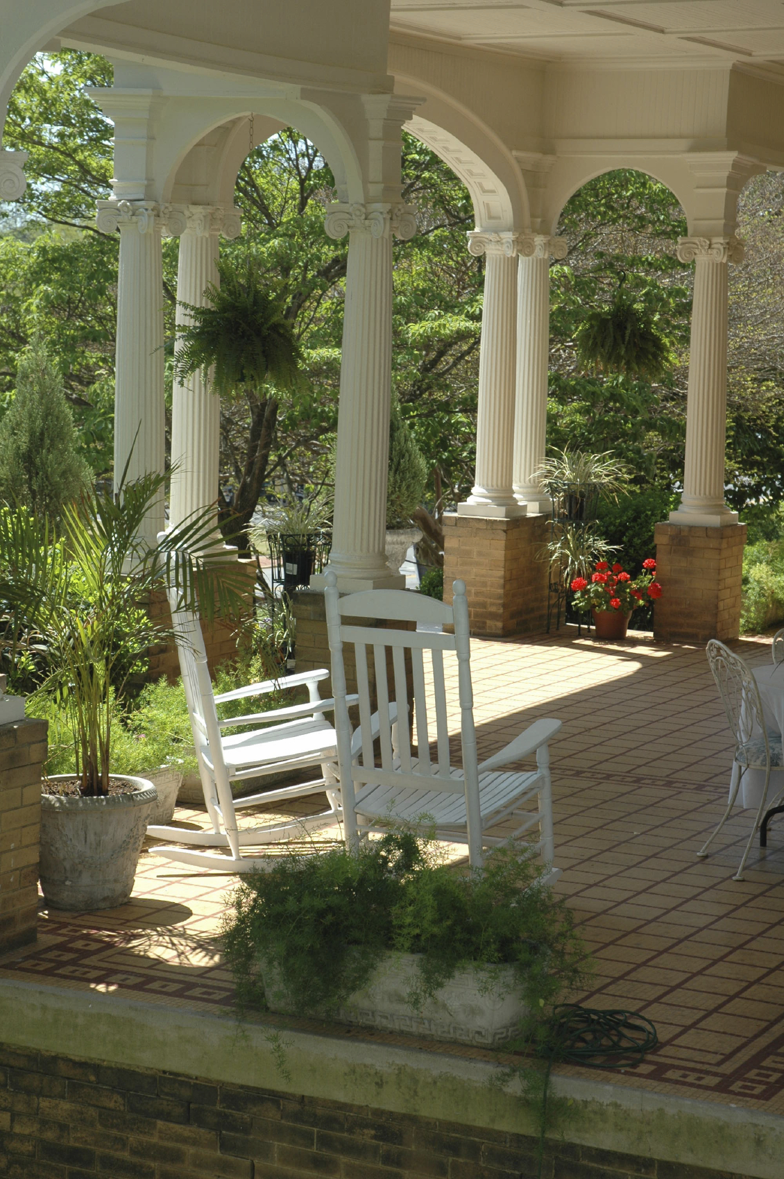 a gorgeous veranda with mosaic tile decking and tall fluted columns on brick supports a - Home Porch Design