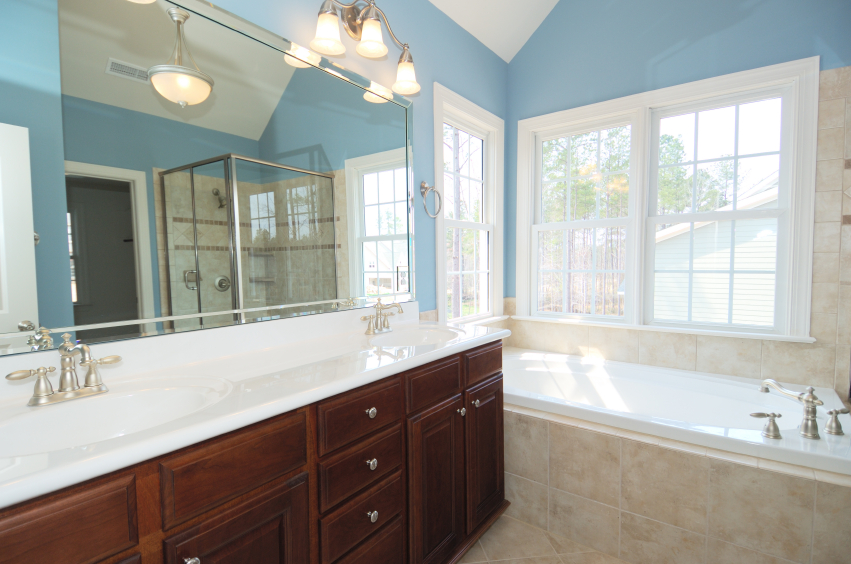 this smaller bathroom has a rich wood vanity with dual sinks and a long mirror with