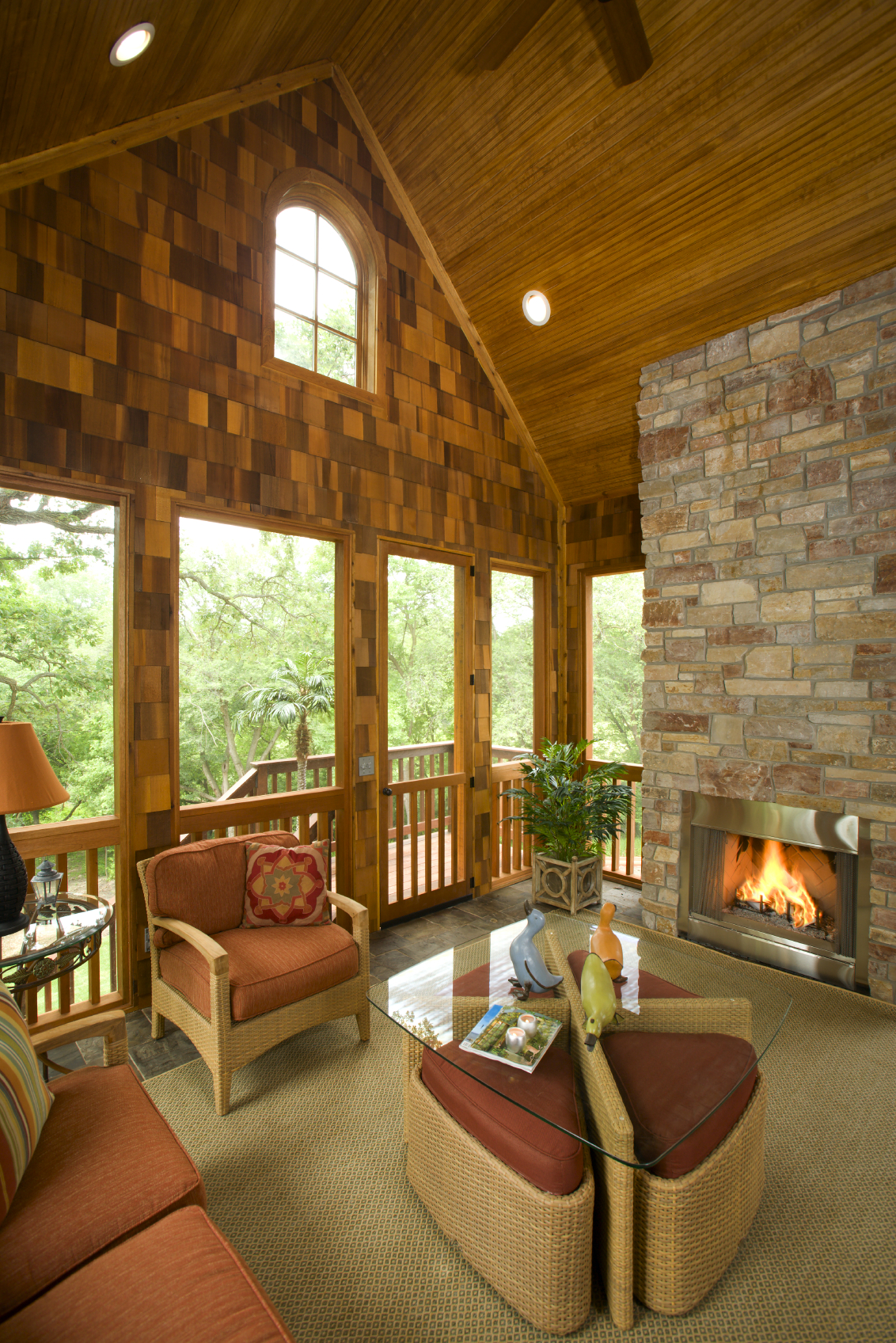 this porch is similar to a covered patio with windows and a fireplace