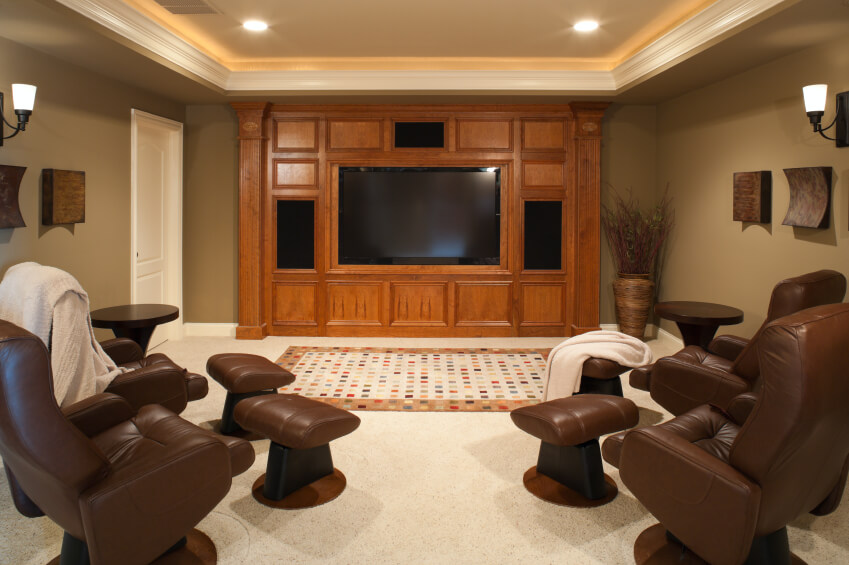 This smaller media room has four recliners with ottomans arranged in a ...