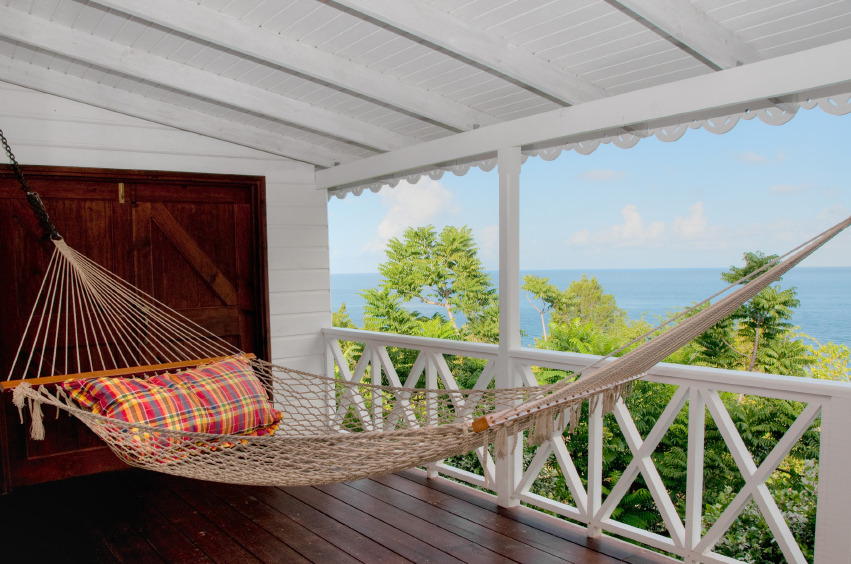 The porch of this cliff-side home features a rope hammock that looks ...