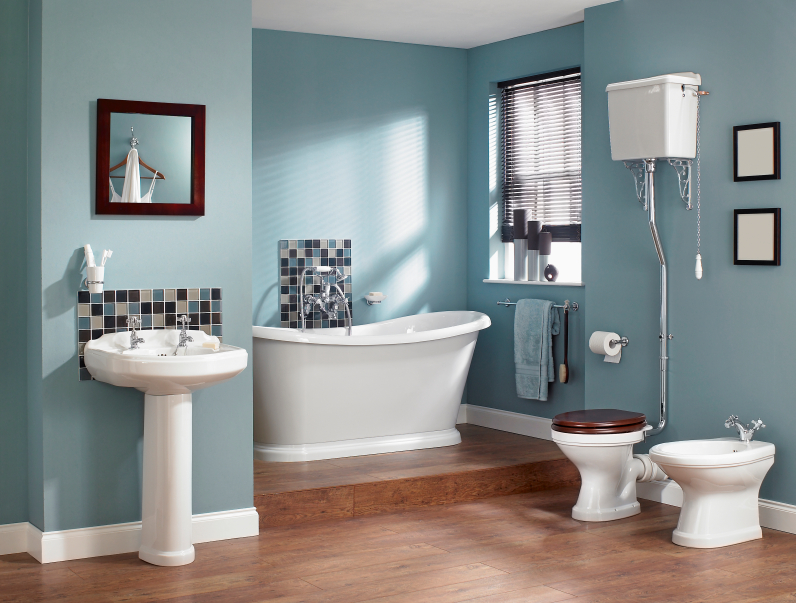 The gorgeous hardwood flooring has two tiers, with the bathtub on a higher tier in a small nook. The soft blue walls are adorned by a small backsplash of multi-colored tile behind the sink and the bathtub. The bath appliance set is a modern twist on vintage plumbing.