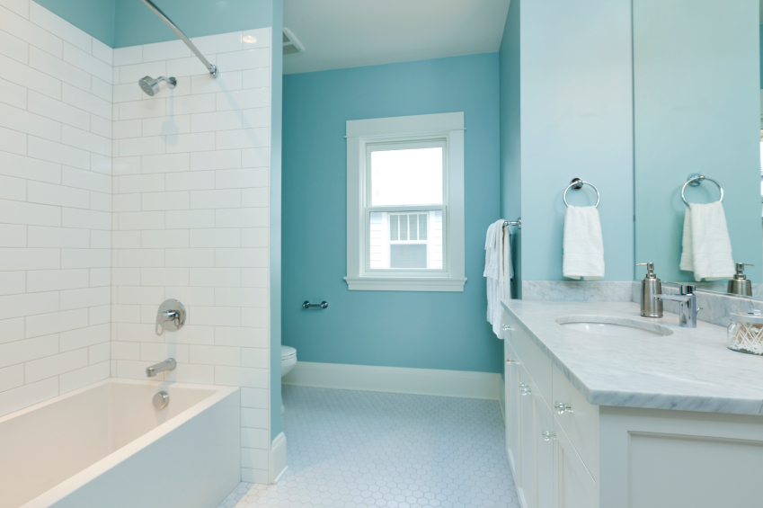 this white and blue bathroom has subway tiles in the bathtub nook marble countertops
