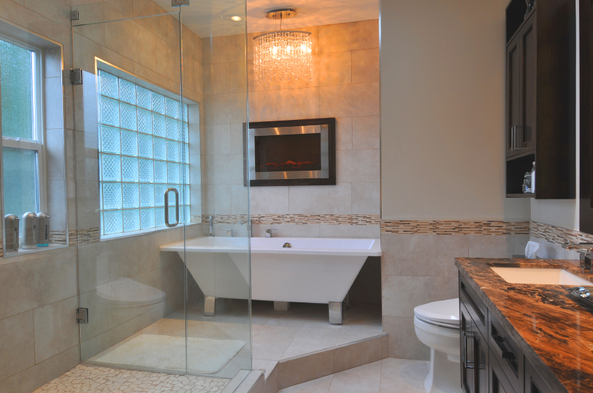 This contemporary styled bathroom features a variety of textures and tones, including a micro-tile detail strip bisecting the walls. Angular white pedestal tub shares space with a glass shower enclosure and rich marbled countertops.