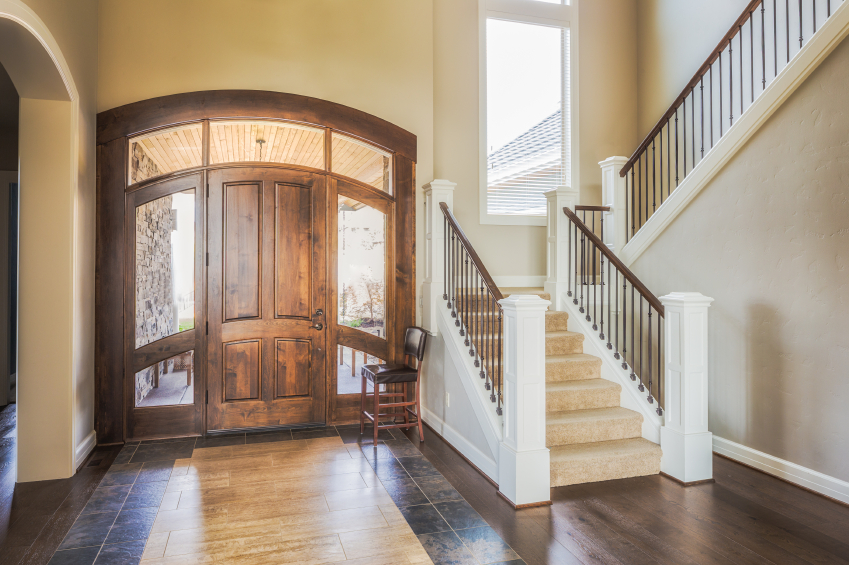 the large rustic entryway leads into a wood and tile entryway with a tight carpeted staircase - Foyer Tile Design Ideas