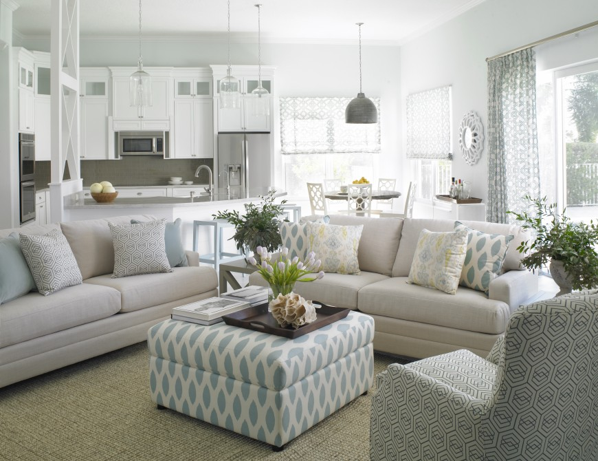 The elegant living room is open to the kitchen and breakfast nook. Layered patterns in shades of blue make another appearance here in the ottoman, reading chair, and the accent pillows on the cream sofas. A tray with spring and coastal accents effectively makes the ottoman into a coffee table.