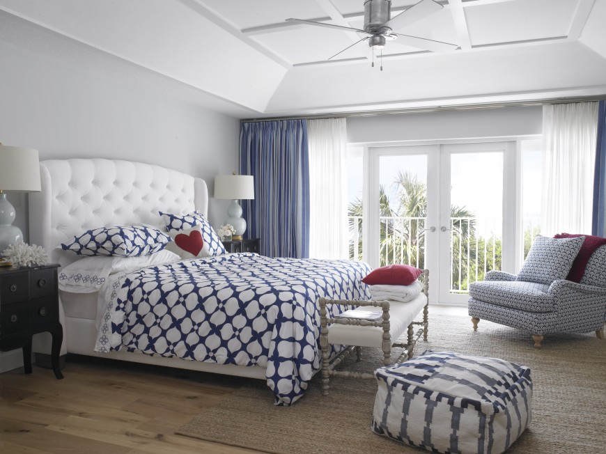 The master bedroom has light hardwood floors and matches a light bench, dark nightstand, and white headboard for a coastal feel. The area rug adds texture, and the layered patterns in blue and gray add to the coastal feeling. The glass double doors lead out onto a small balcony that overlooks the owner's boat.