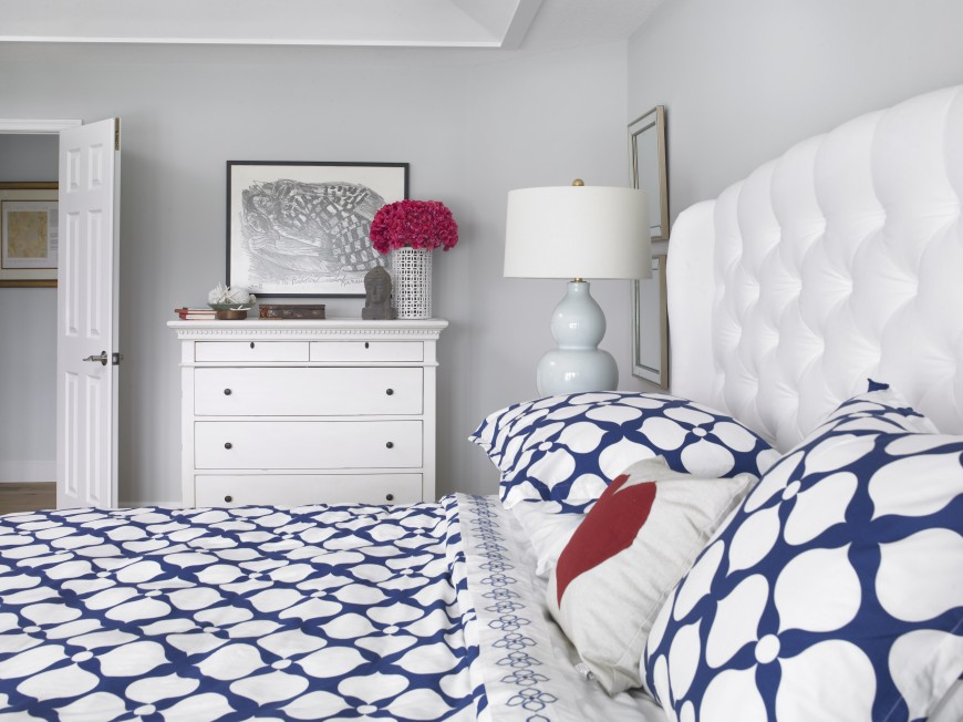 A close up of the bedding shows the button-tufted headboard, the bright, large pattern of the bedding, and the small dresser to the left of the bed with bright accents.