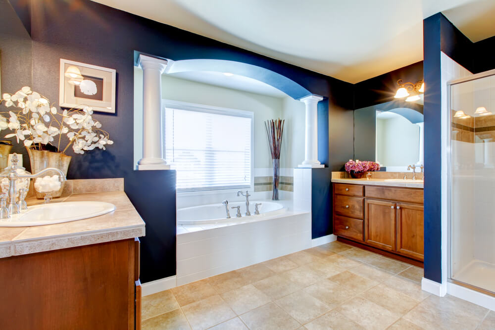 The dark navy walls are a stark contrast to the white tile around the bathtub. Half-columns on either side of the bathtub add elegance.