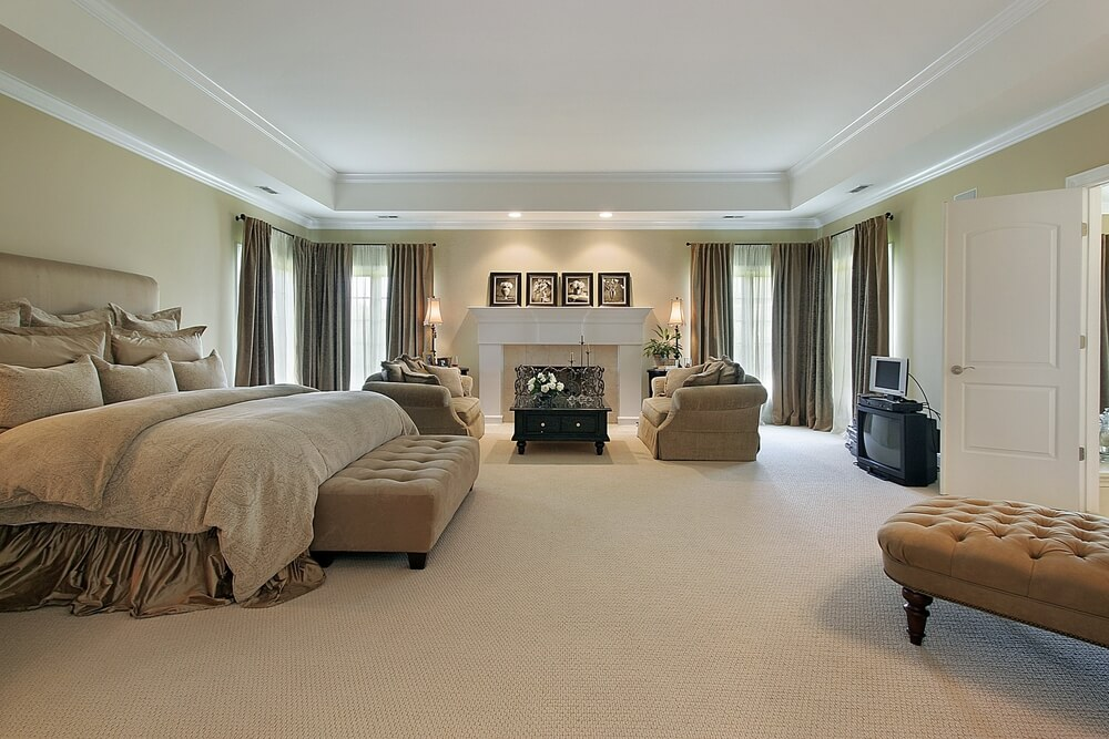 this spacious carpeted master bedroom has an enormous tray ceiling