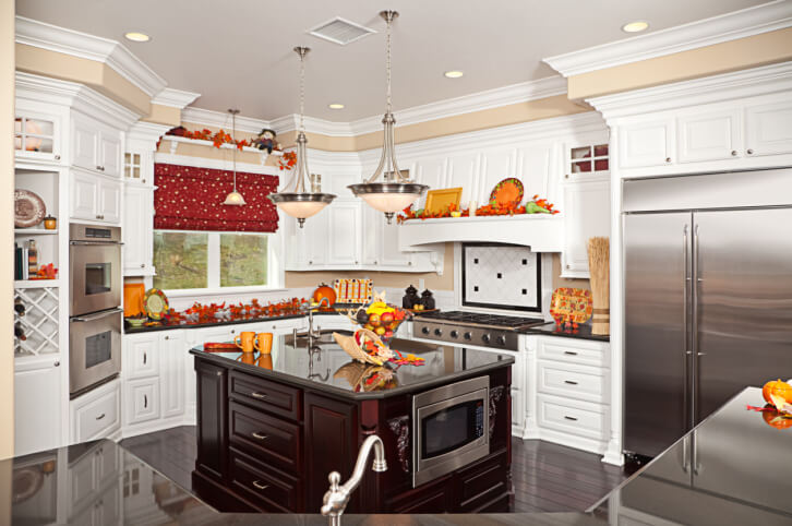 A bright white country kitchen decorated for Thanksgiving in bright oranges, reds and yellows. Small glass-front cabinets at the very top of the room are perfect for displaying small items. The dark wood island contrasts beautifully with the pristine white cabinetry in the rest of the room.