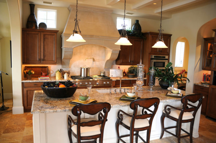 An elegant eat-in kitchen of modest size, featuring a large granite island with a white base. The rest of the cabinets in the kitchen are a light natural wood. Mounted on the wall behind the stove is a long faucet that's perfect for filling up heavy stockpots that don't fit well in the sink.