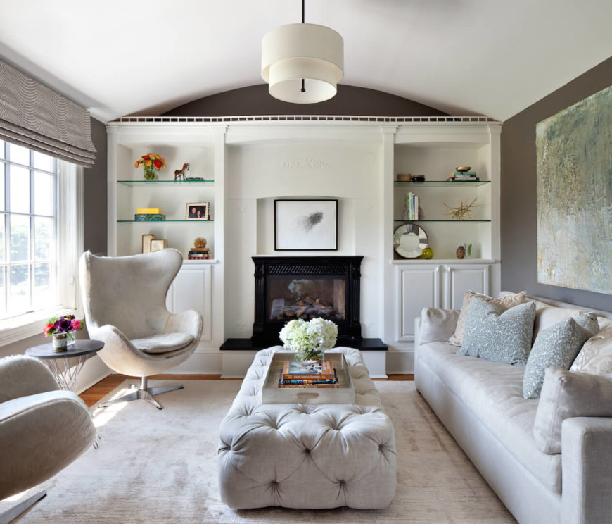 The sitting room adjacent to the master suite has several cozy and furry chairs, a beige sofa, and a beautiful button-tufted upholstered ottoman. A metallic tray on top allows the ottoman to double as a coffee table. On the far wall is an enclosed fireplace and built-in shelving.