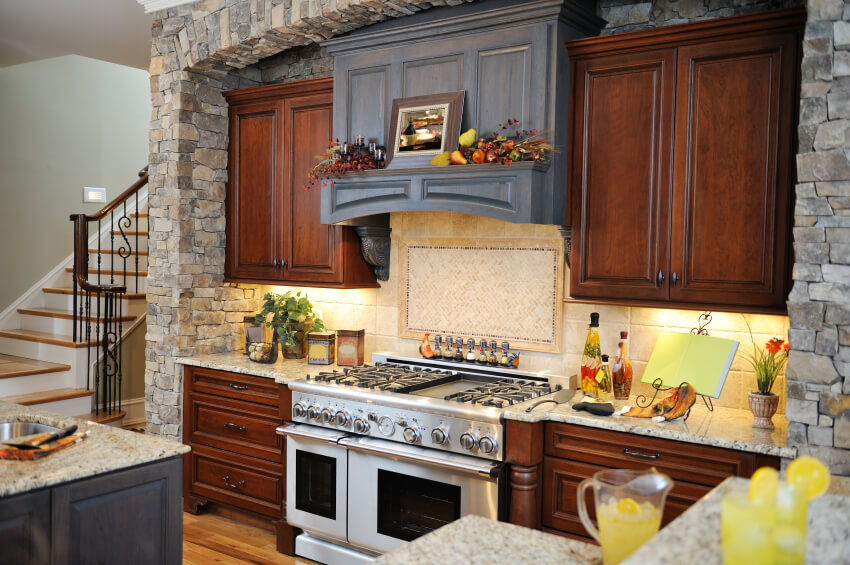 A French country kitchen with contemporary flair. The polished wooden cabinets with small, delicate pulls are matched with a muted blue vent hood and a beige tile backsplash. The same muted blue makes a second appearance on the kitchen island. On either side of the kitchen area are layered stone walls that both visually separate the room from the others and add an element of rustic style.