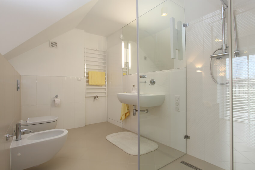 A white modern bathroom with a ladder towel rack and sleek chrome fixtures. The glass-enclosed shower is in white glass mosaic tile.